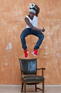 Dodzi Dougban, eine Schwarzer tauber Mann, der über einem dunkelbraunen, gepolsterten Holzstuhl vor einer unsauber gestrichenen orangenen Wand hoch in die Luft springt. Er trägt rote Nike-Schuhe, Jeans, ein weißes ärmelloses Shirt, eine graue und schwarze Mütze sowie einen weißen Nike-Handschuh an seiner über den Kopf erhobenen rechten Hand.
