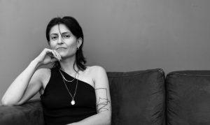 Schwarz-weiß Fotographie von Rita Mazza, einer weißen, taube, italienischen Frau, die in die Kamera blickend auf einer Couch sitzt, ihren Kopf auf ihrer rechten Hand auf der Armlehne aufgestützt. Sie trägt ein schwarzes Oberteil, das ihre linke Schulter freilässt, eine Strähne ihres dunklen Haares fällt in ihr Gesicht zwischen ihre Nase und ihr linkes Auge. Sie trägt lackierte Nägel, ein Tattoo aus schwarzen Linien auf ihrem linken Arm sowie drei Halsketten und einen Ring an ihrem rechten kleinen Finger.